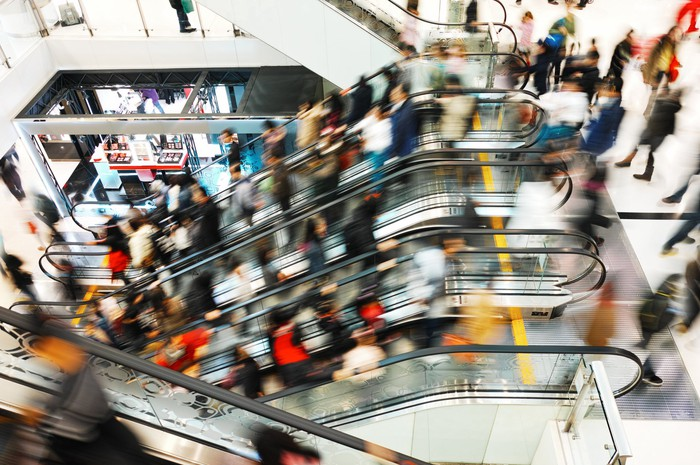 Bank of escalators full of people at a busy shopping mall.