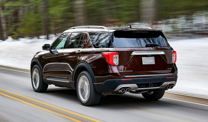 A dark red 2020 Ford Explorer Platinum on a snowy road, viewed from a rear three-quarter angle.