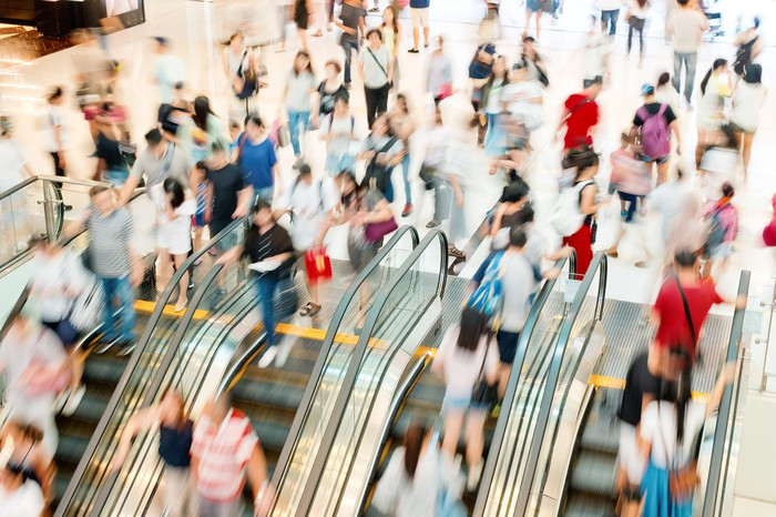 A blurred group of shoppers moving up and down escalators at a shopping mall