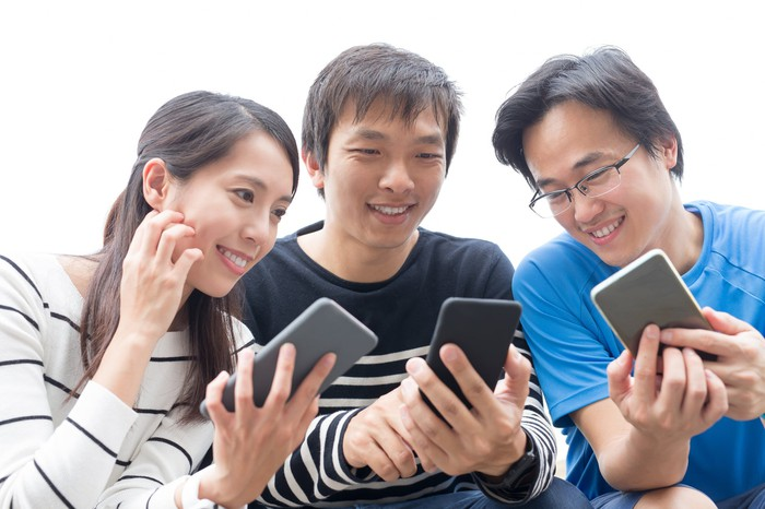 Three young people smiling and looking at each other's smartphones.