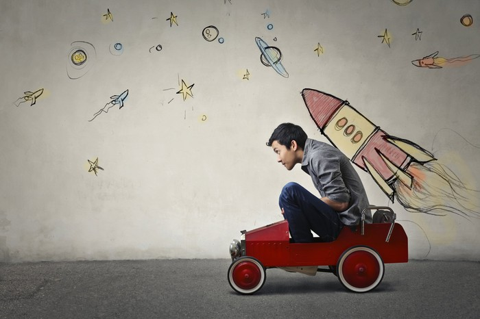 A man in a toy car with a rocket ship drawn on a wall behind him.