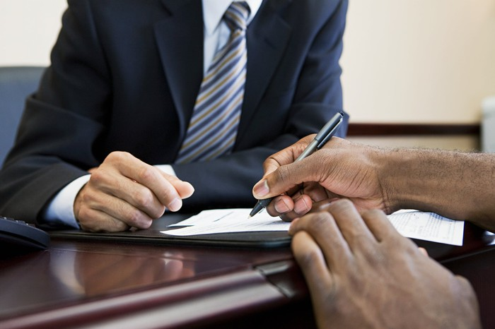 A person signs paperwork as man in a suit looks on.