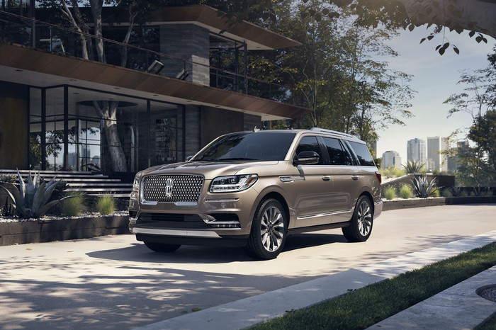 A gold Lincoln Navigator in front of a building