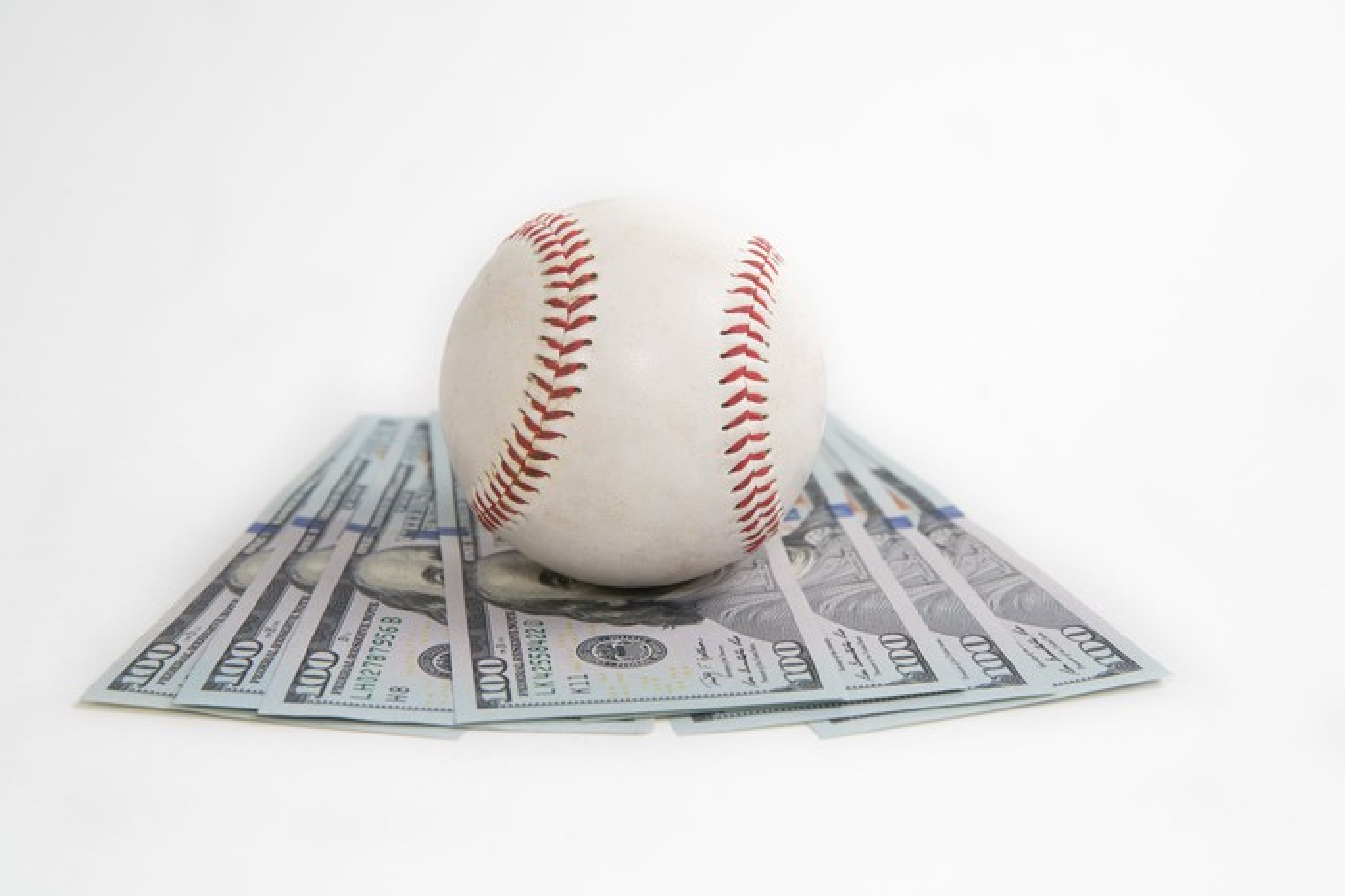 Baseball on top of $100 bills
