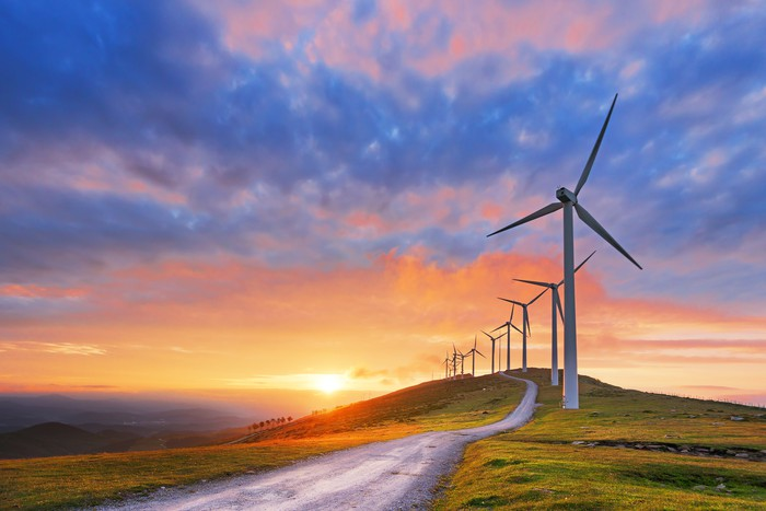 A row of wind turbines with the sun setting in the background.