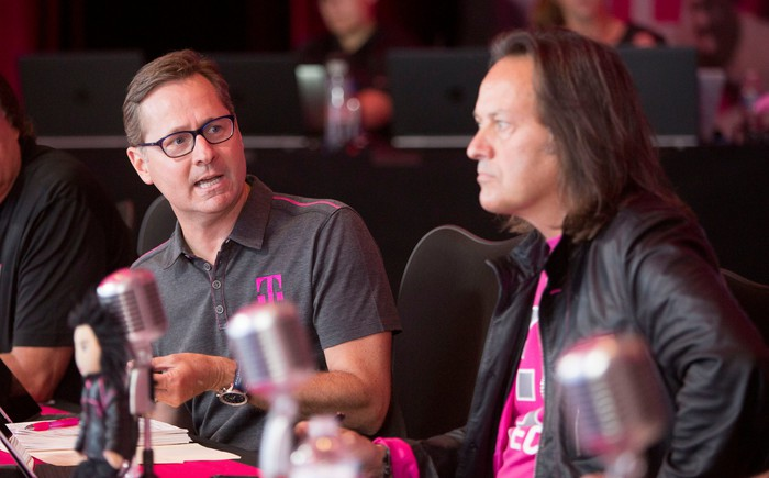 T-Mobile COO Mike Sievert and CEO John Legere sitting at a table with microphones in front of them