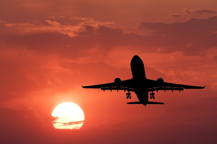 A plane flying in a sky at sunset.