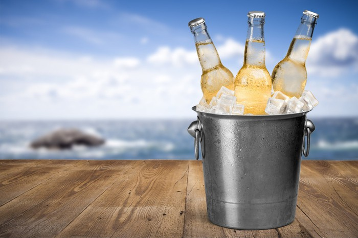 A bucket of beers on a deck with the ocean in the background.