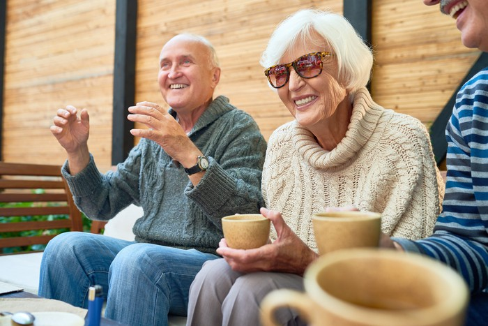 Smiling older woman in sunglasses sitting between two men.