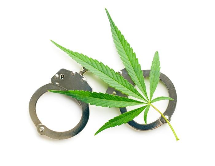 A marijuana leaf and a set of handcuffs.