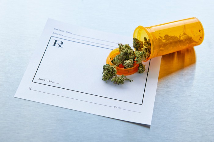 Marijuana buds spill out of a bottle onto a prescription pad.