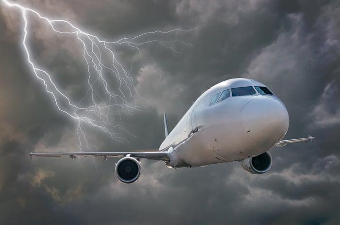 A jetliner flies toward the viewer through dark clouds and a lightning strike.
