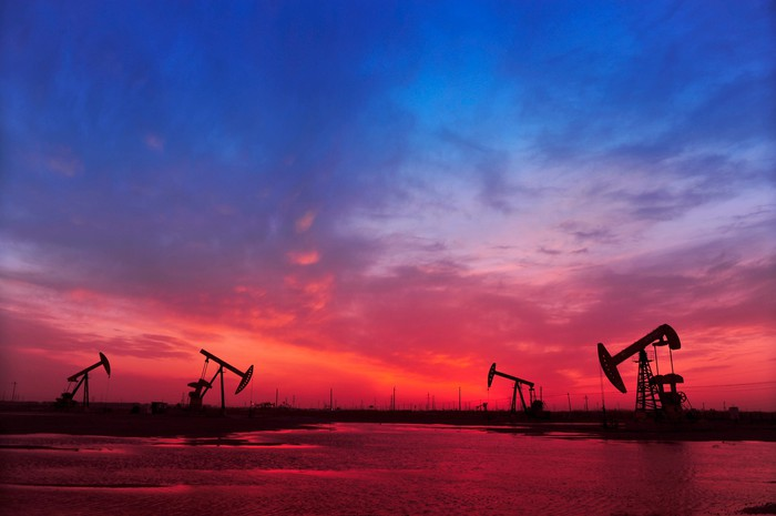 Oil wells in silhouette against a sunset.