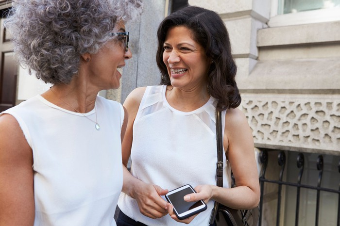 Two professionally dressed women walking and laughing.