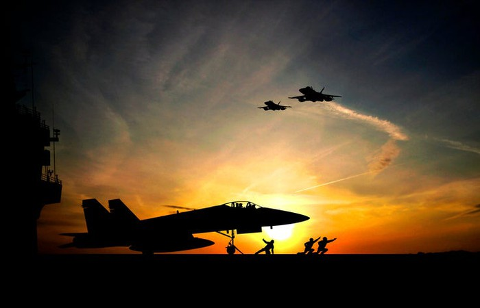 Fighter jet taking off from aircraft carrier at sunset.