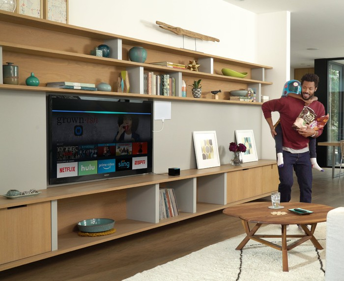 A man holding a child in a living room with a Fire TV displaying on the television.
