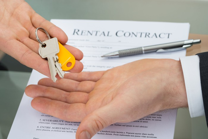 A person handing over house keys with a rental contract in the background.