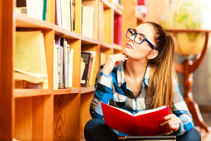 A young woman in a college library that's holding a book open while in deep thought.
