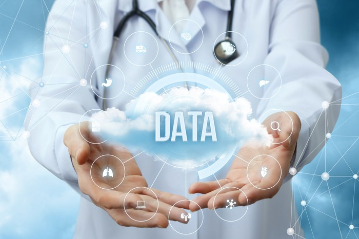 Medical worker shows the data cloud on blurred background.
