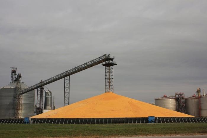 A pile of corn outside a grain elevator.