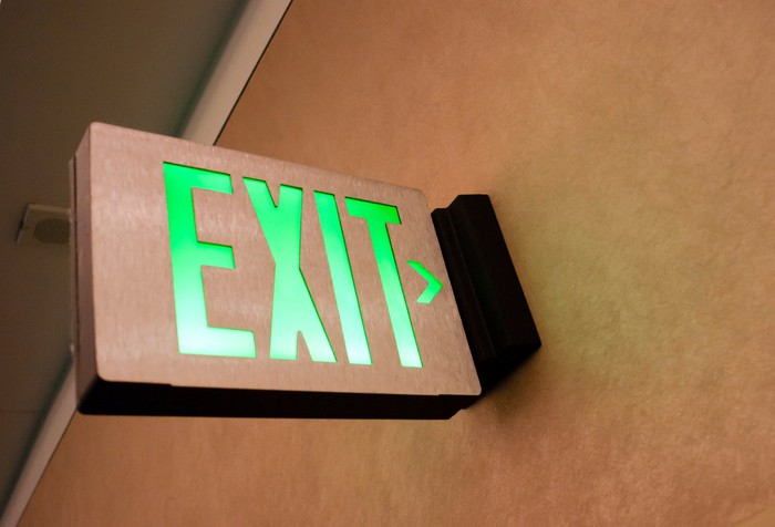 An illuminated exit sign above a door.