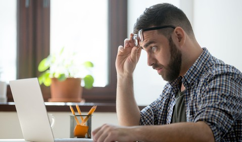 Worried man looking at computer