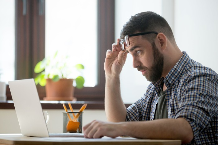 Worried man raising eyeglasses from his eyes while looking at his laptop.