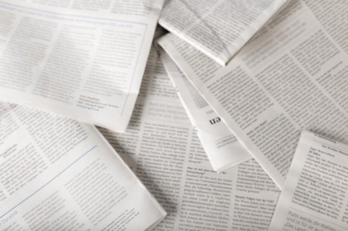Scattered newspapers on a desk.