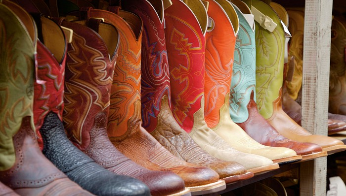 A row of cowboy boots for sale at a western store.