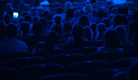 Audience in a darkened theater in silhouette