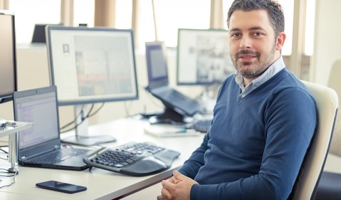 smiling man at an office desk_GettyImages-505769612
