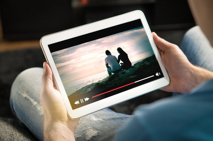 Hands holding a tablet displaying a streaming video