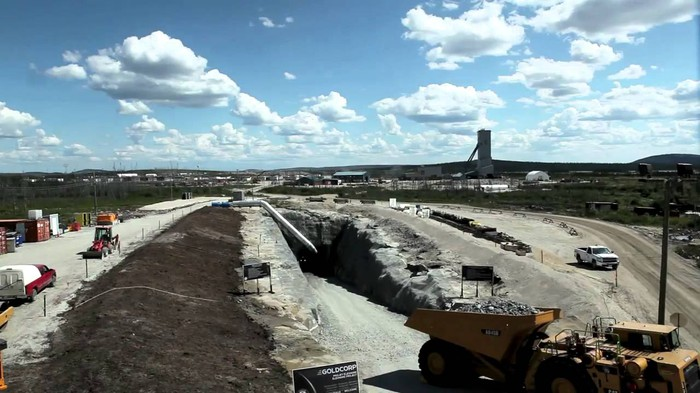Mining site with trucks and equipment moving ore and materials near a refining plant.
