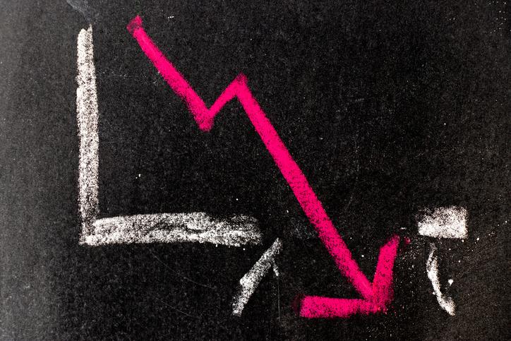 A declining pink arrow on a chart drawn on a chalk board.