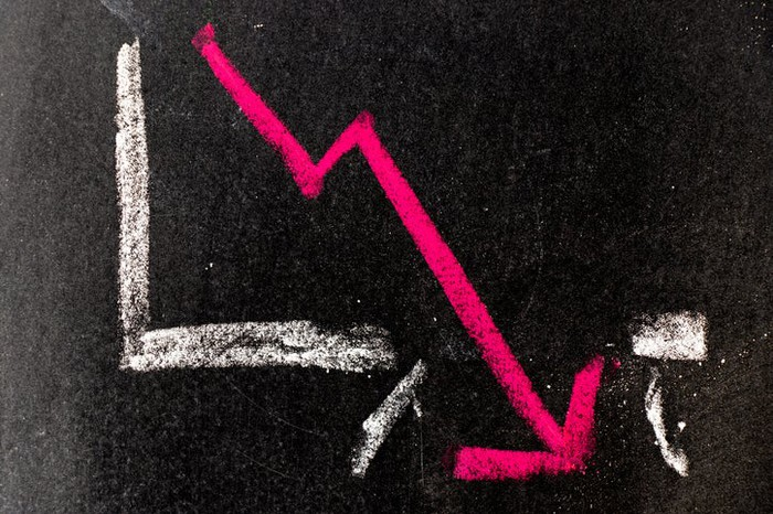 A declining pink arrow on a chart drawn on a chalk board.