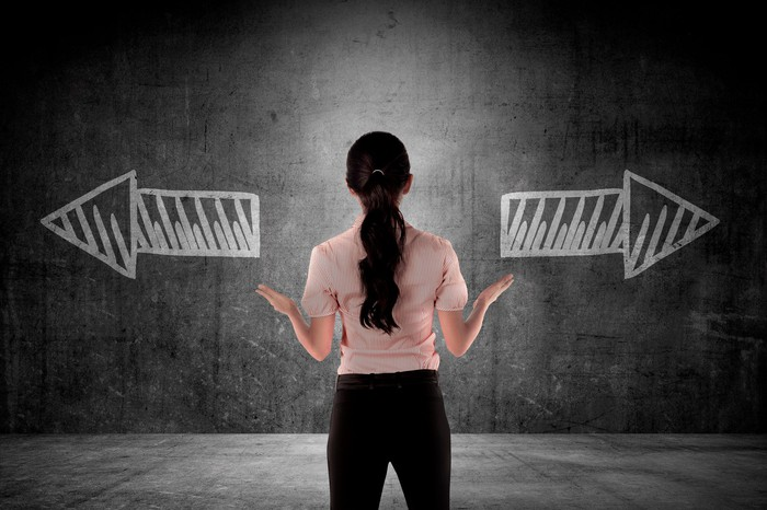 Woman facing a wall with two arrows in chalk pointing in different directions.
