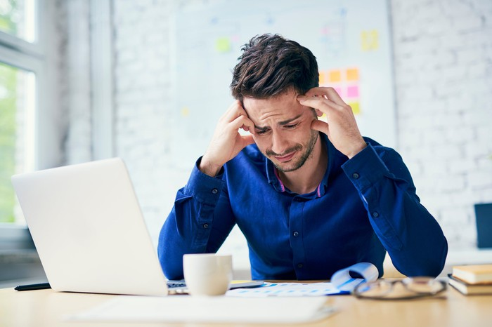 Man at laptop holding his head and scrunching his face