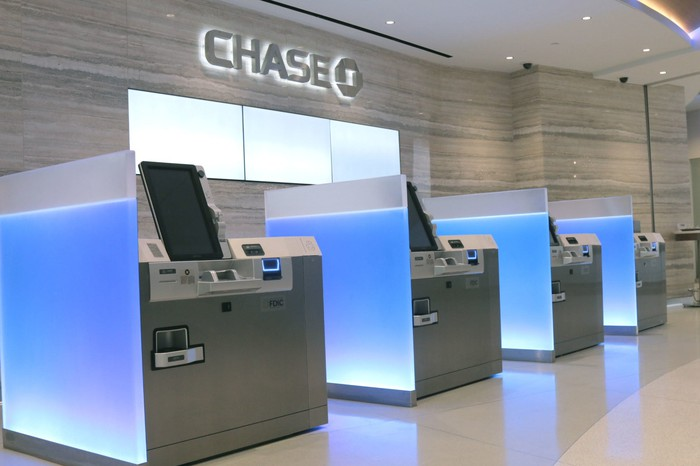 Interior of a Chase banking branch with four ATMs lined up against a wall.