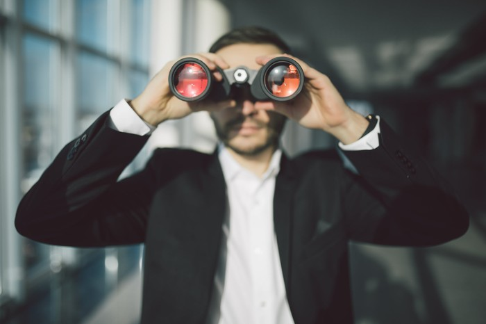 Person in business suit looking through binoculars