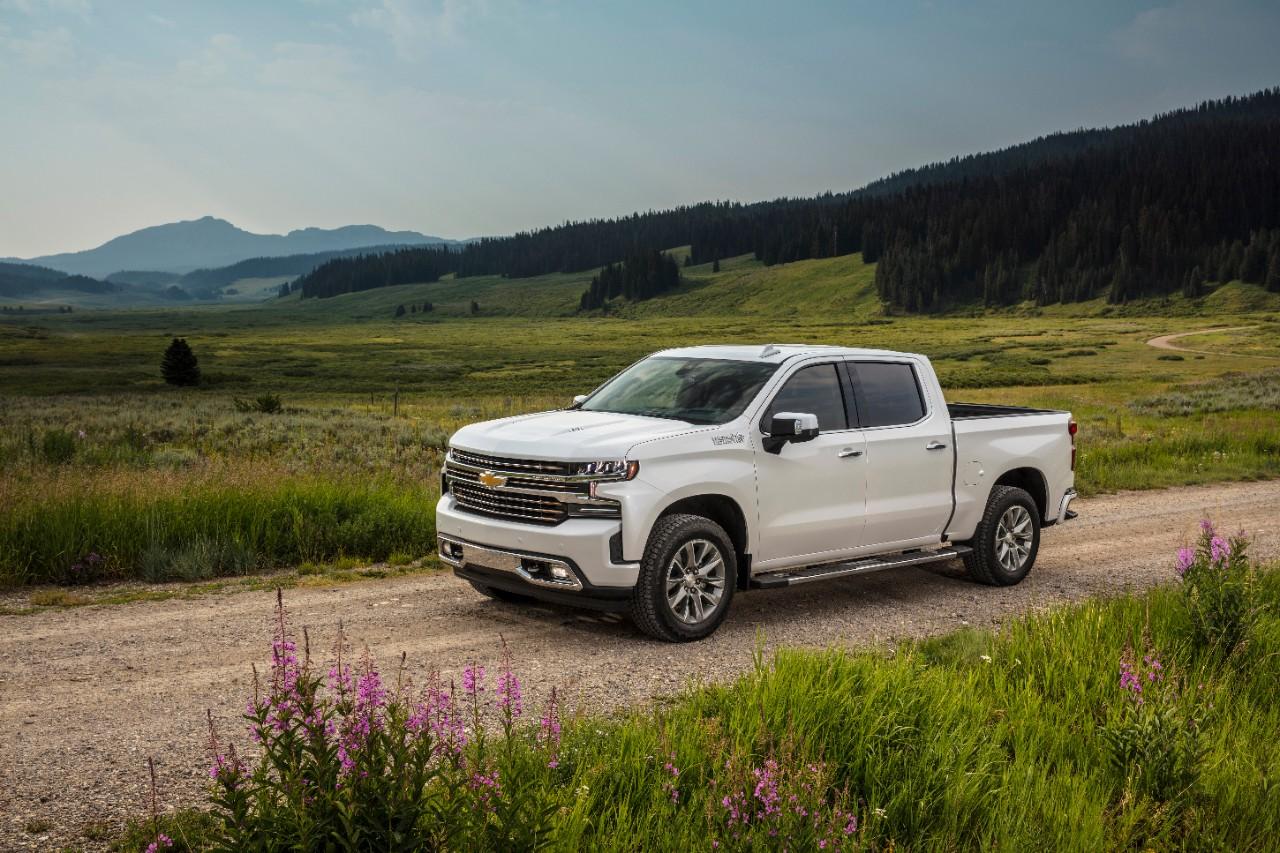 A white Chevy Silverado pickup on a dirt road