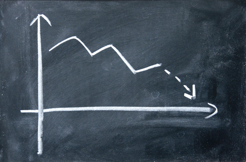 Chalkboard chart with a downward trending arrow.