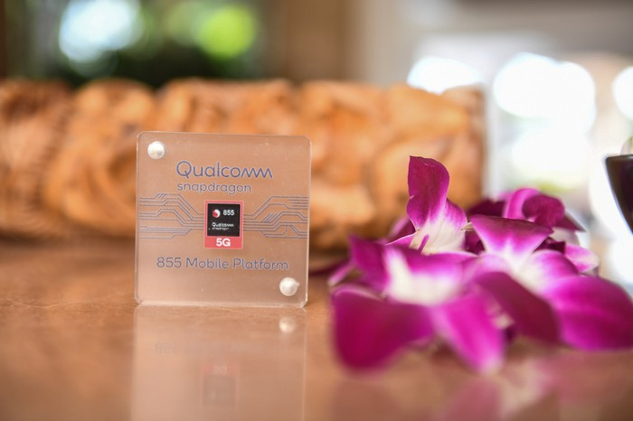 A Qualcomm Snapdragon chip next to a bunch of purple flowers.