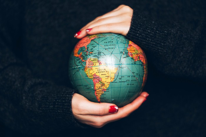 Woman's hands with red nail polish holding small globe.