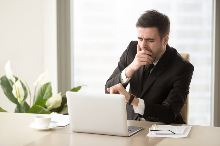 Man in suit yawning at desk
