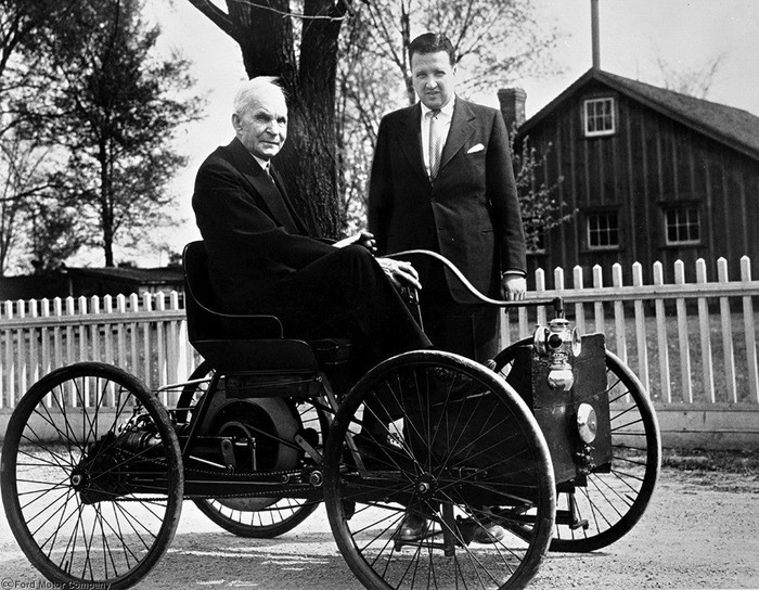 A black and white photo showing an elderly Henry Ford seated in a very early Ford car, with Henry Ford II standing alongside.