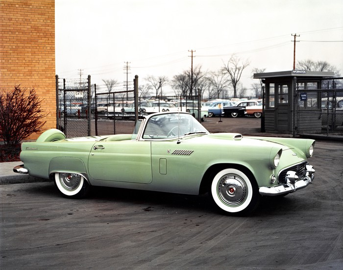 A green 1956 Ford Thunderbird, a low-slung two-seat convertible, is shown parked outside a building in 1956.