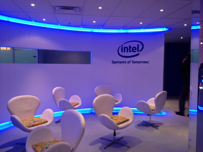 Room with six chairs, neon lights, and curved wall with Intel logo on it.