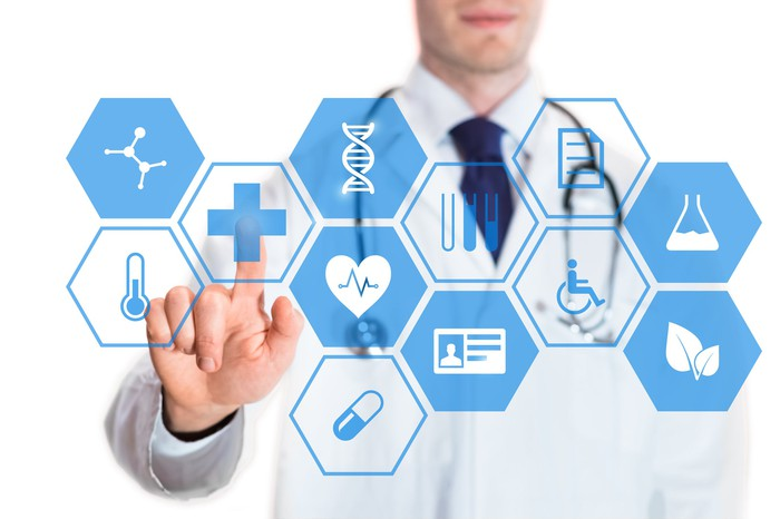 A person in a lab coat touching a virtual interface button of healthcare application.