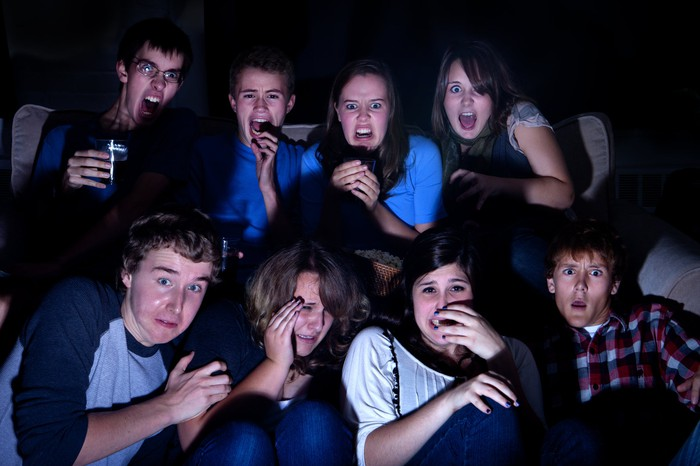 A group of people watch a horror movie on tv.