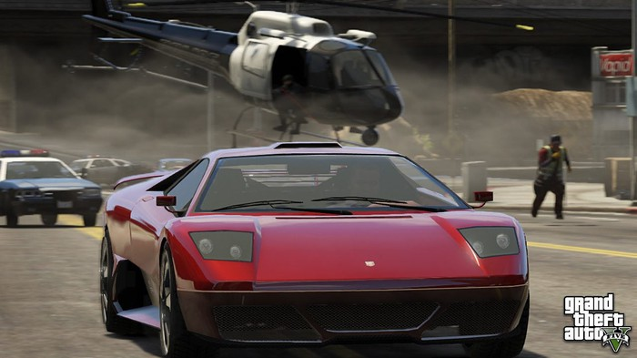 A screen shot from Grand Theft Auto 5 showing a red sports car being chased by police cars and a helicopter.